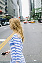 USA, New York, Manhattan, Young woman walking in the street, holding mobile phone - GIOF01887