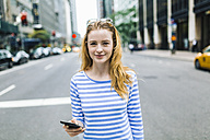 USA, New York, Manhattan, Young woman walking in the street, holding mobile phone - GIOF01890