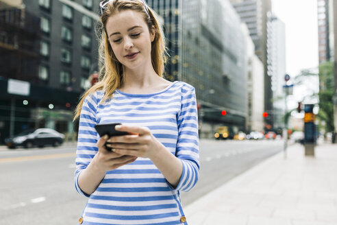 USA, New York, Manhattan, Young woman walking in the street, holding mobile phone - GIOF01893