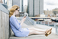 Young woman sitting at pier using mobile phone - GIOF01917