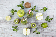 Two glasses of green smoothie and ingredients on wood - JUNF00857