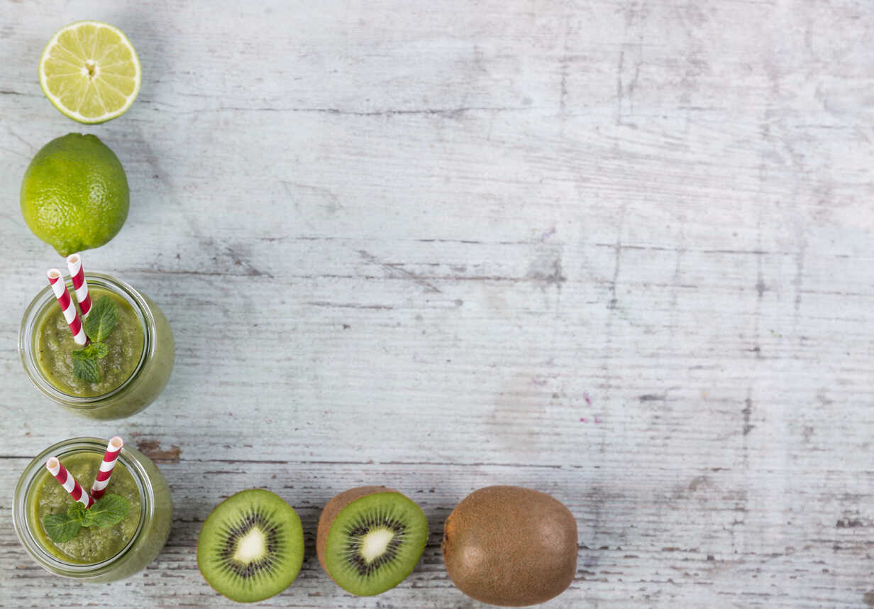 Two glasses of green smoothie and ingredients in a row on wood - JUNF00860 - JLPfeifer/Westend61