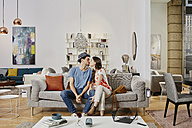 Couple in modern furniture store sitting on couch, kissing - RORF00578