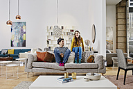 Couple in modern furniture store sitting on couch, laughing - RORF00584