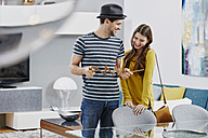 Couple in furniture store measuring dining table with pocket rule - RORF00587