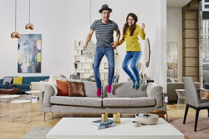 Couple in modern furniture store jumping on couch - RORF00593