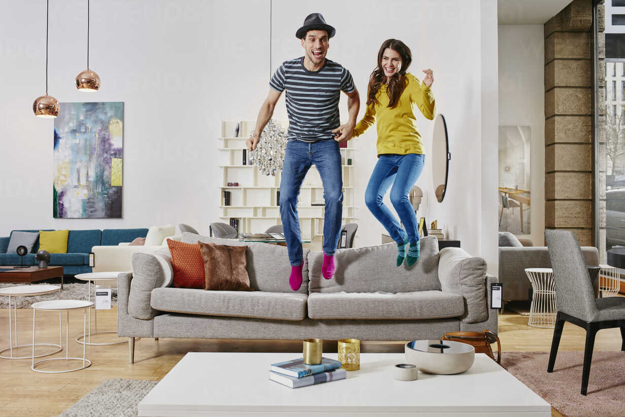 Couple in modern furniture store jumping on couch - RORF00593 - Roger Richter/Westend61