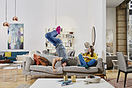 Couple in modern furniture store doing headstand on couch - RORF00596