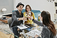 Couple celebrating sales contract in furniture store - RORF00614