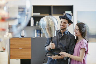 Couple in furniture store choosing lamp - RORF00626