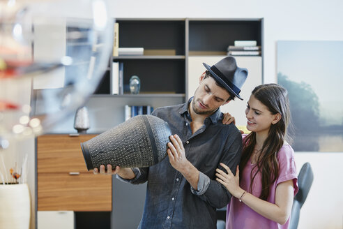 Couple in furniture store looking at vase - RORF00629