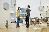 Happy couple carrying new arm chair out of furniture store - RORF00638