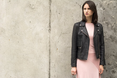Portrait of young woman wearing black leather jacket and pink dress in front of concrete wall - LMF00640