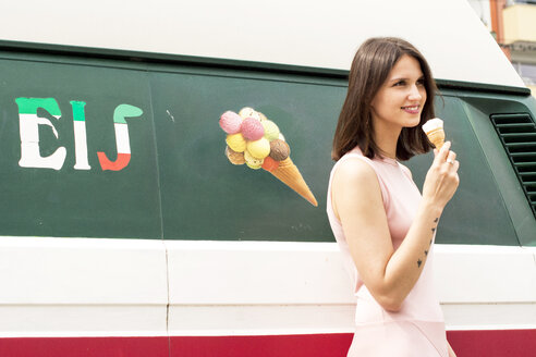 Smiling young woman with ice cream cone in front of ice cream van - LMF00649