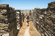 Greece, Mykonos, Delos, woman walking along the old houses at archaeological site - GEMF01510