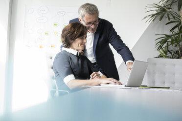 Businessman and businesswoman using laptop in office together - RBF05624