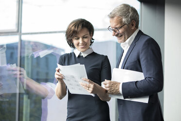 Smiling businessman and businesswoman looking at documents at the window - RBF05627