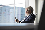 Businessman using cell phone in office - RBF05630
