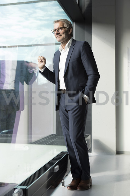Confident businessman looking out of window - RBF05633