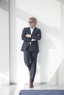 Confident businessman leaning against a wall - RBF05636