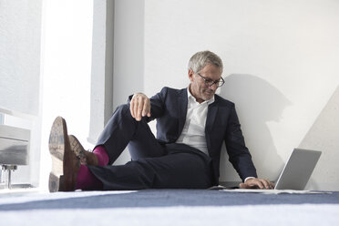 Businessman sitting on the floor using laptop - RBF05639