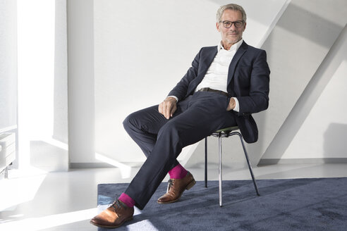 Confident businessman sitting on chair - RBF05642