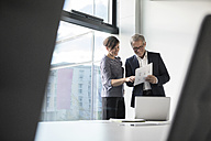 Smiling businessman and businesswoman looking at documents in office - RBF05645