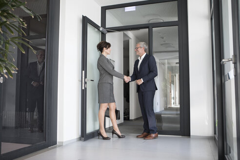 Businessman and businesswoman shaking hands in office corridor - RBF05651