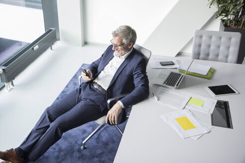 Smiling businessman using cell phone in office - RBF05660