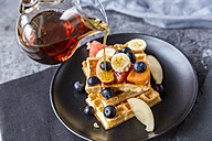 Pouring maple sirup on waffles with various fruits - SARF03189