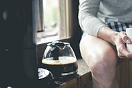 Man sitting next to coffee pot on window sill - ZOCF00151