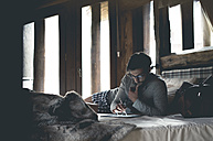 Young man using tablet lying in bed at home - ZOCF00154