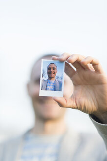 Man's hand holding instant photo of himself, close-up - SKCF00261