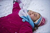 Smiling girl making a snow angel - LOMF00514