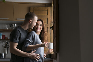 Amorous couple standing in kitchen, embracing with cup of coffee - KKAF00451