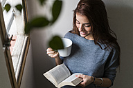 Attractive young woman reading book and drinking coffee - KKAF00472
