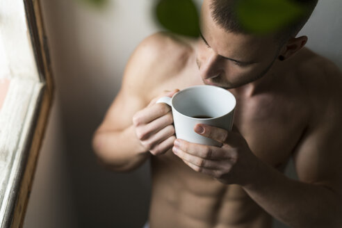 Attractive young amn with six pack drinking coffee - KKAF00481
