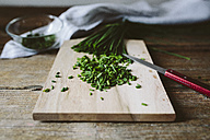 Chopped and whole chives and kitchen knife on wooden board - GIOF01934