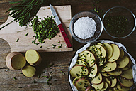 Slices of potatoes with chives, red peppercorns and salt in baking pan - GIOF01937