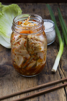 Glass of Kimchi, ingredients and chopsticks on dark wood - LVF05886