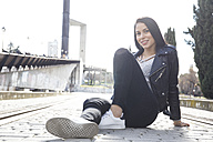 Portrait of smiling young woman wearing black leather jacket sitting on pavement - ABZF01934