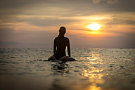 Indonesia, Bali, female surfer in the ocean at sunset - KNTF00636