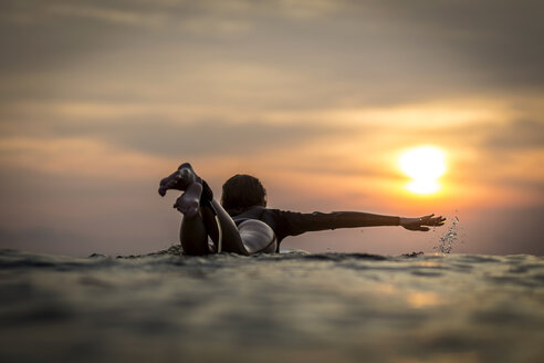 Indonesia, Bali, female surfer in the ocean at sunset - KNTF00639