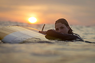 Indonesia, Bali, portrait of female surfer in the ocean at sunset - KNTF00642