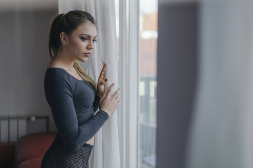 Portrait of young woman looking through the window - LCUF00092