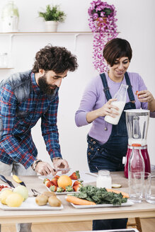 Couple preparing smoothies with fresh fruits and vegetables - JRFF01206