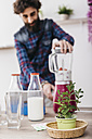 Man preparing smoothies with fresh fruits and vegetables at home - JRFF01215