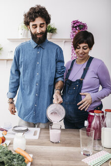 Couple pouring prepared fruit smoothie into a glass - JRFF01218