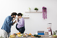 Couple drinking glass of healthy fruit smoothie together in the kitchen - JRFF01221