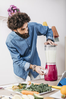 Man preparing smoothie with fresh fruits and vegetables at home - JRFF01233